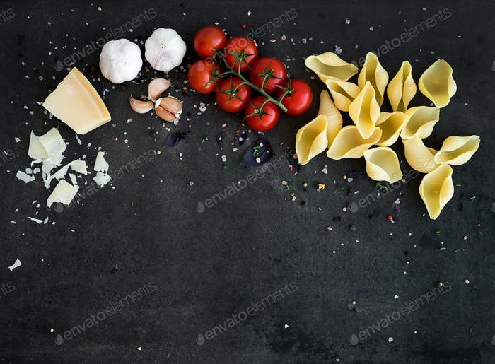 Food frame. Pasta ingredients on dark grunge backdrop, copy space