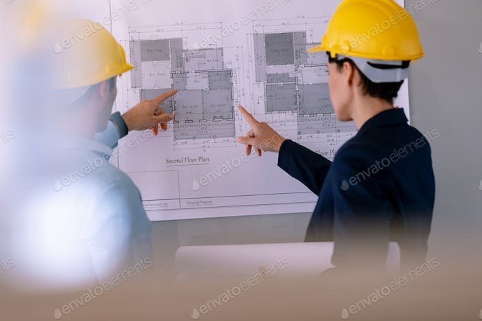 Rear view of Caucasian architects discussing over blueprint on glass board in a modern office