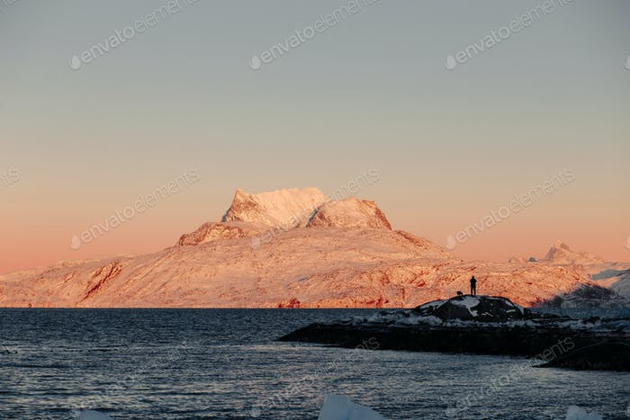 Snowcapped mountain and sea at sunset