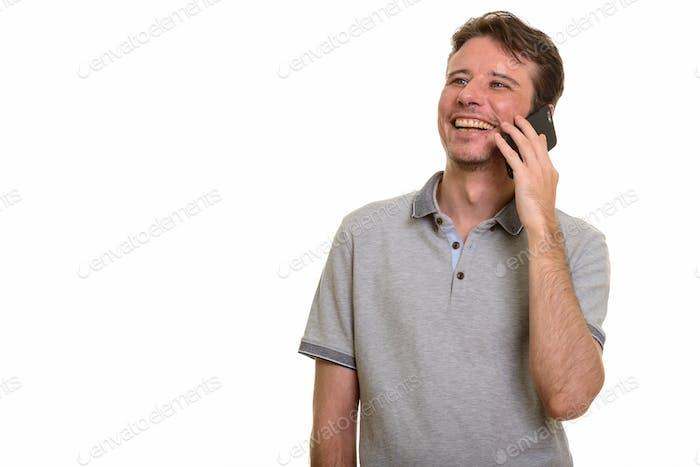 Happy Caucasian man talking on mobile phone