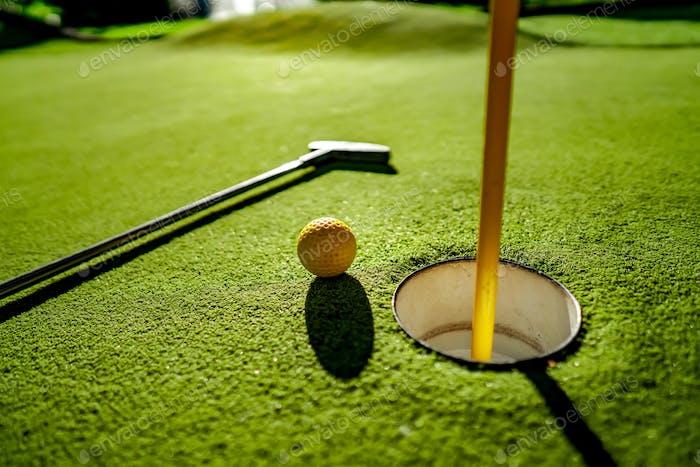 Mini Golf yellow ball with a bat near the hole at sunset