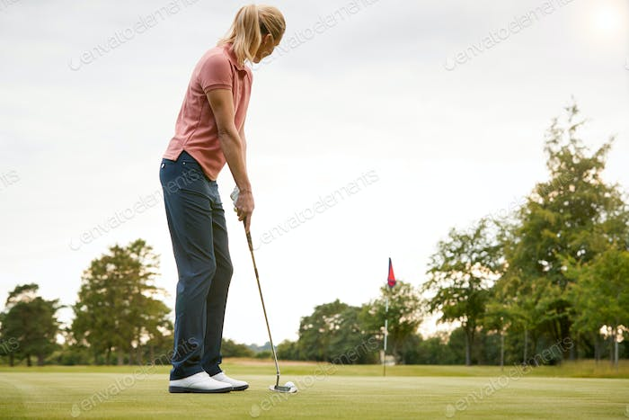 Rear View Of Female Golfer Putting Ball On Green