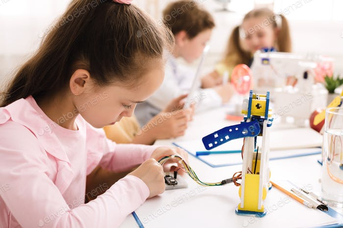 Girl working with wires and circuits on robotics project