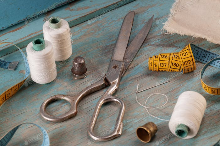 Retro sewing accessories on blue wooden background