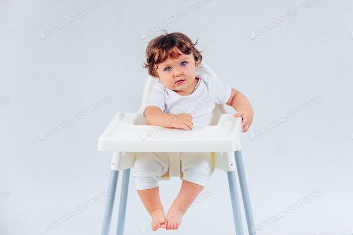 Thumbnail for Happy baby boy sitting on studio background