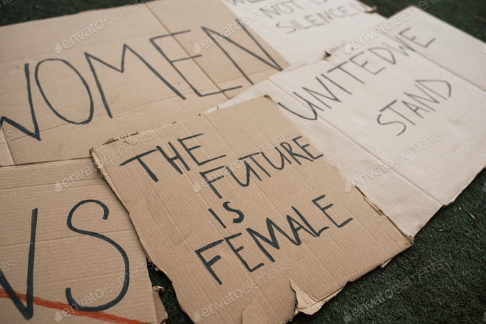 Handmade signs. Group of banners with different feminist quotes lying on the ground