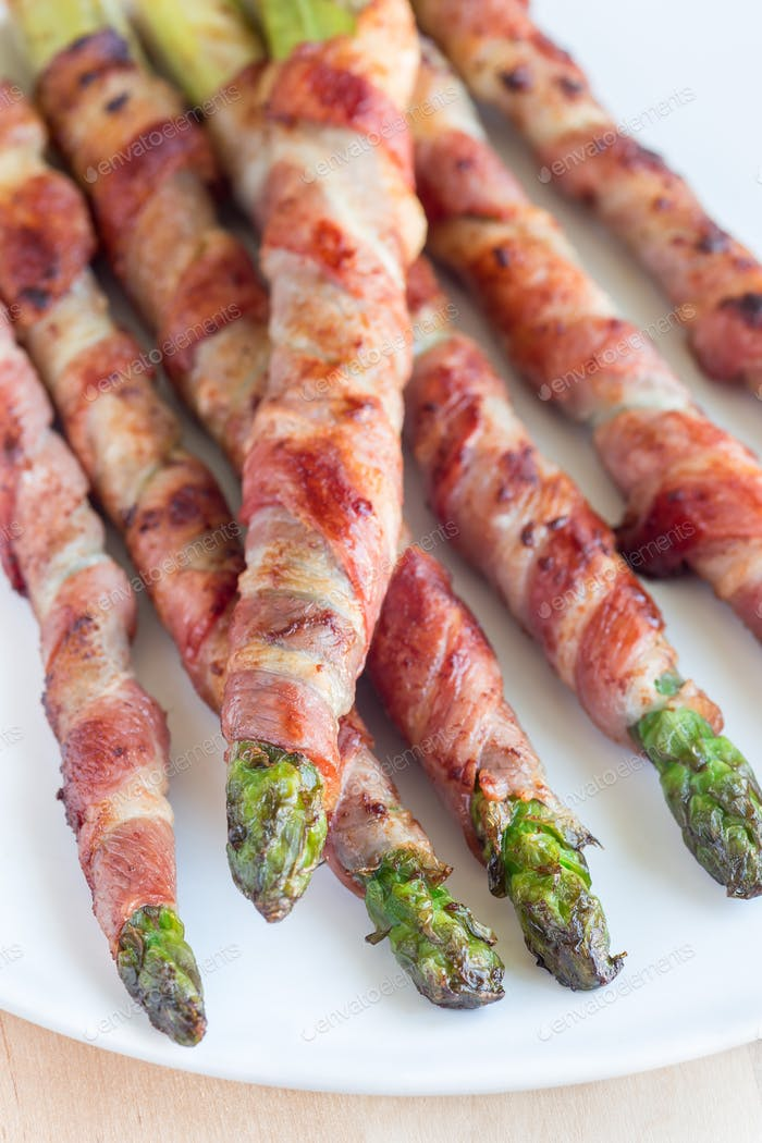 Healthy appetizer, green asparagus wrapped with bacon on white p