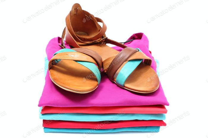 Woman sandals on pile of colorful clothes. White background
