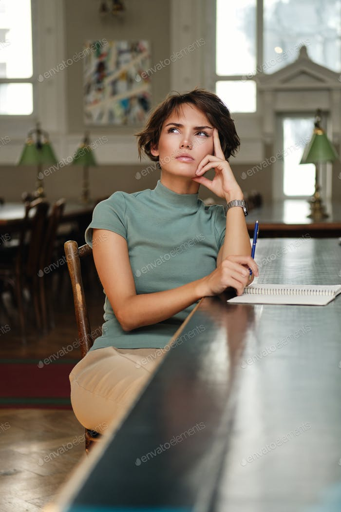 Serious thoughtful student girl sitting in library of university thinking about something