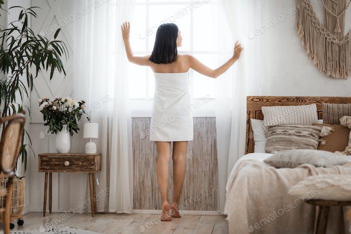 Slim asian woman looking through window in bedroom