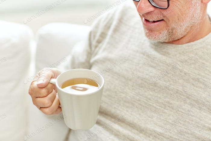 close up of happy senior man drinking tea at home