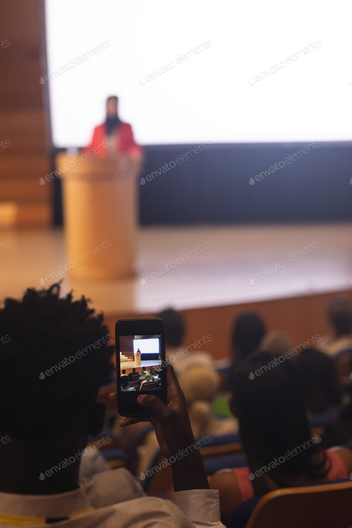 Man with smartphone taking video clip of businesswoman in the auditorium
