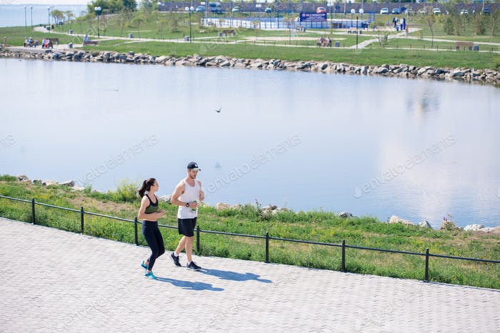 Couple Jogging in City Park Background