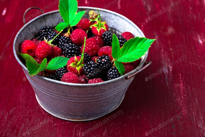 Blackberry and raspberry in a metal bowl on red wooden background