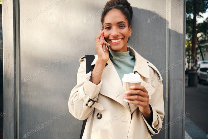 Happy African American girl in trench coat joyfully looking in camera talking on cellphone