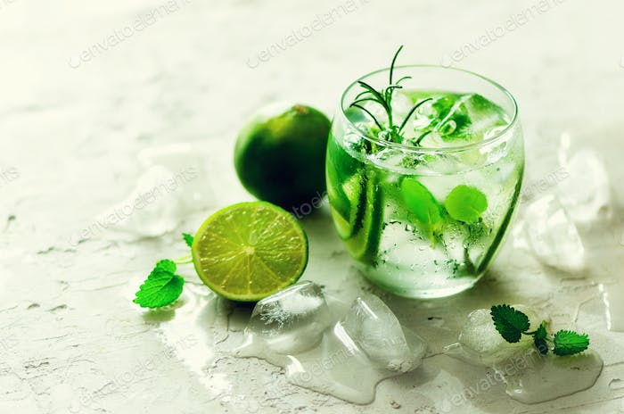 Homemade lime lemonade with cucumber, rosemary and ice, white background. Cold beverage, detox water