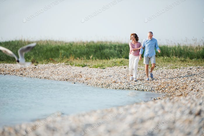 Senior couple on a holiday walking by the lake. Copy space.
