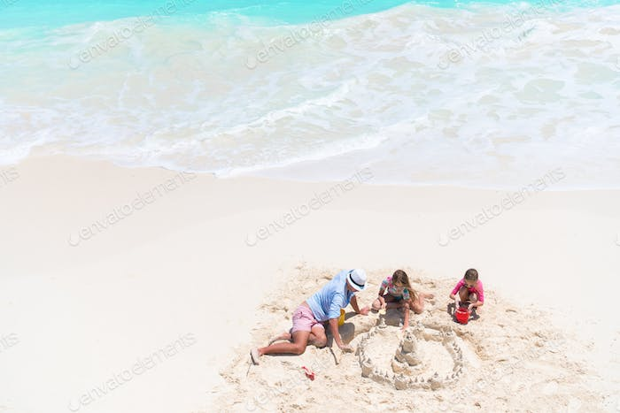 View from above to father and little daughters making sand castle at tropical beach