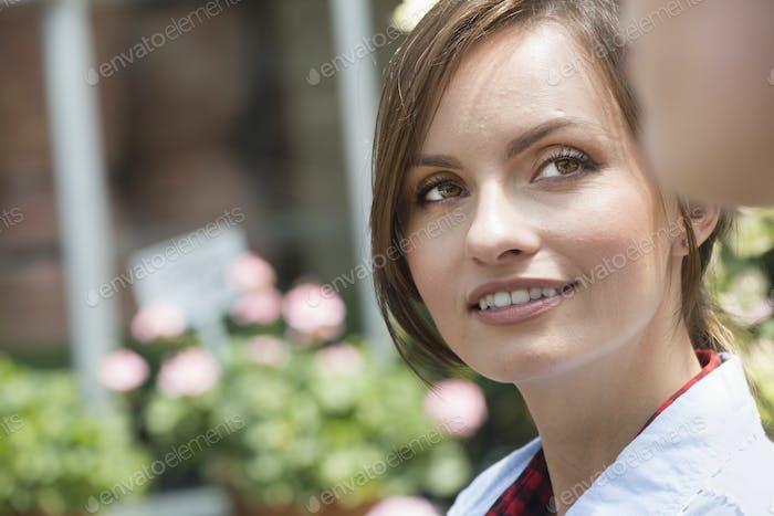 Eine junge Frau, die seitwärts auf einen Gefährten blickt.