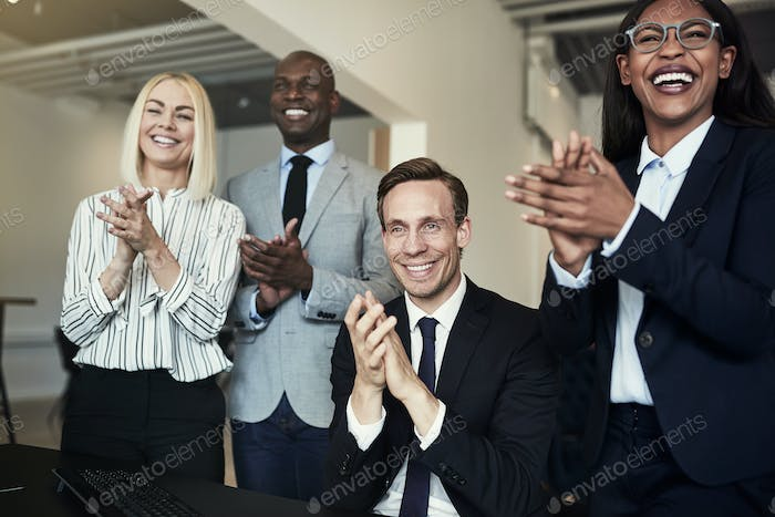 Group of businesspeople smiling and clapping after an office presentation