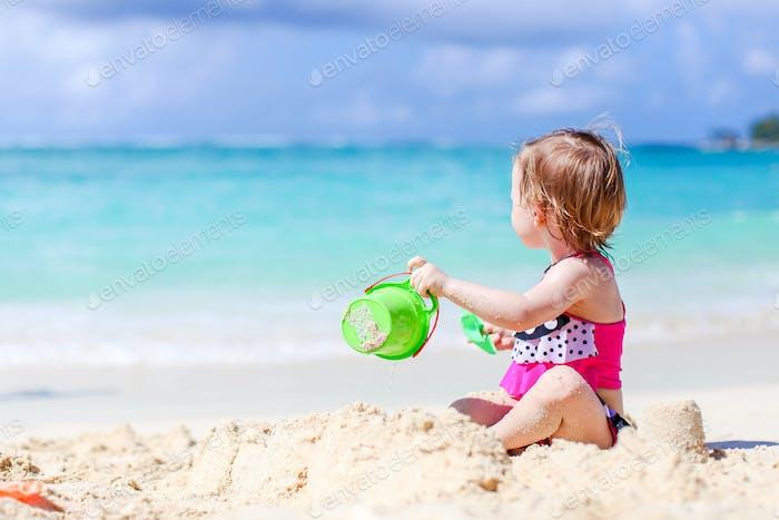 Kleines Mädchen am tropischen weißen Strand machen Sandburg