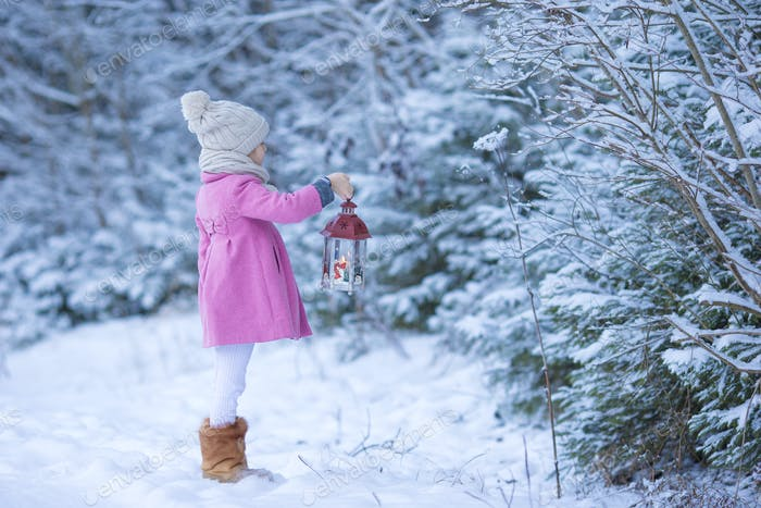 Adorable little girl with flashlight on Christmas at winter forest outdoors