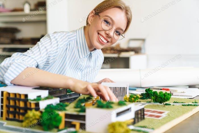 Photo of joyful young woman architect designing draft with house model