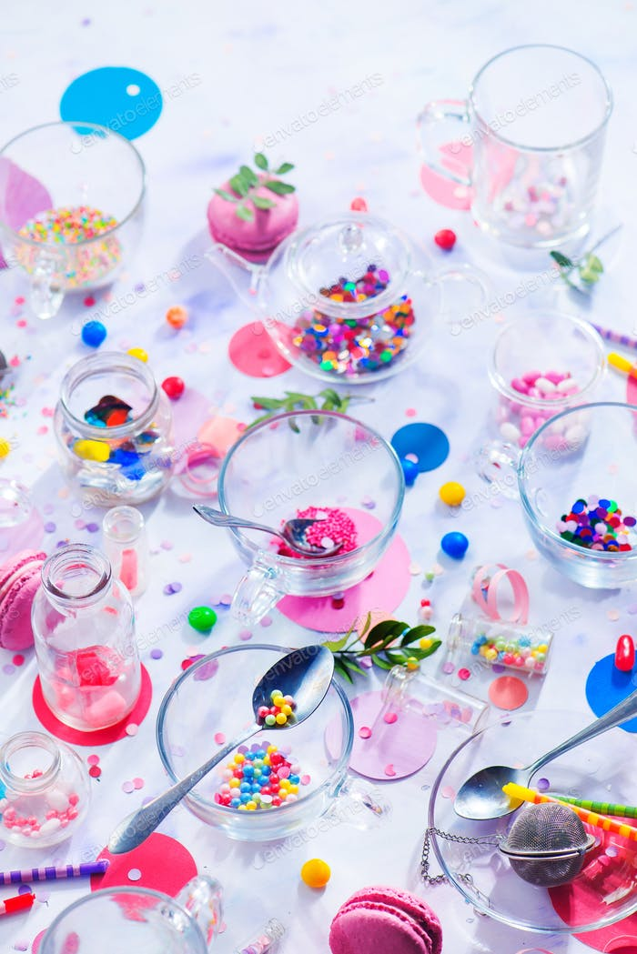 Party supplies in glass tea cups. Sprinkles, confetti, candies, macaroons and birthday candles on a