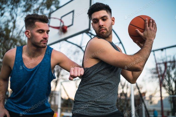 Dos jóvenes amigos jugando al baloncesto.