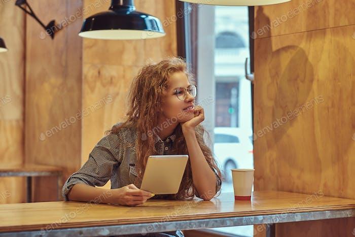 Junge intelligente lockige Mädchen Student sitzt an einem Tisch in der College-Kantine während einer Pause.