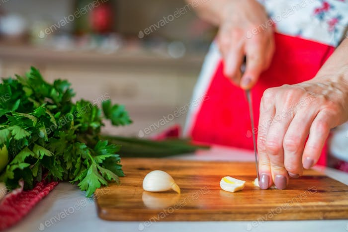 Female hand with knife chops garlic in kitchen. Cooking vegetables