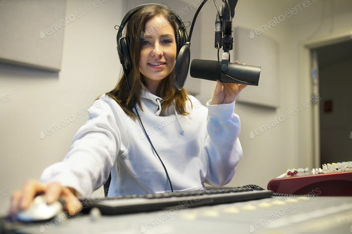 Confident Female Jockey Using Technologies In Radio Studio