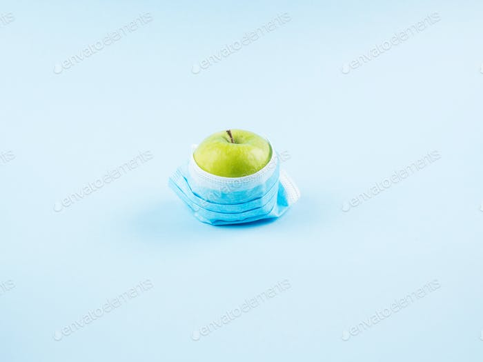 Green fresh apple in face mask. Covid19 concept
