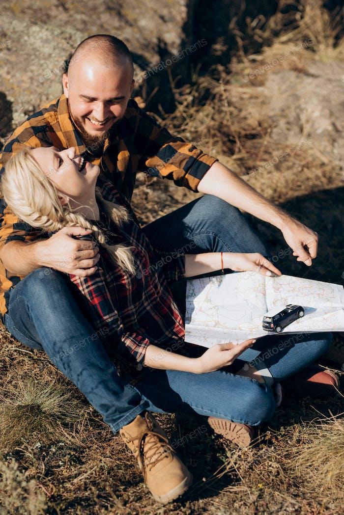 Glatzkopf mit Bart und einem blonden Mädchen schaut auf die Karte und sucht nach
