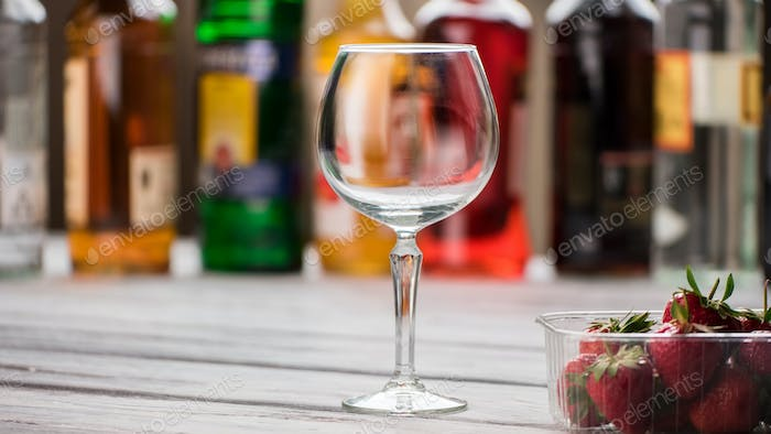 Empty wineglass and strawberries