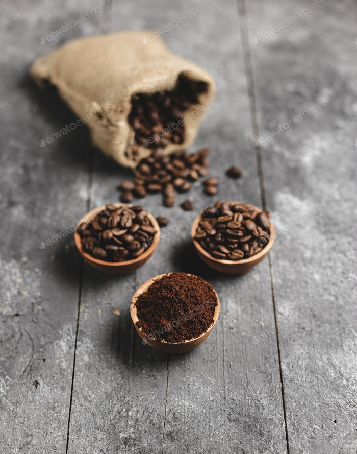 ground coffee beans in wood saucer and bag with grunge black background
