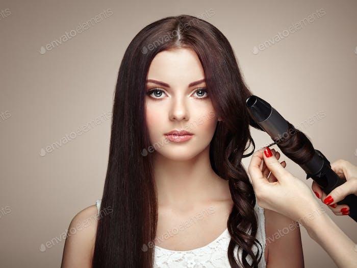 Hairdresser woman curls her hair