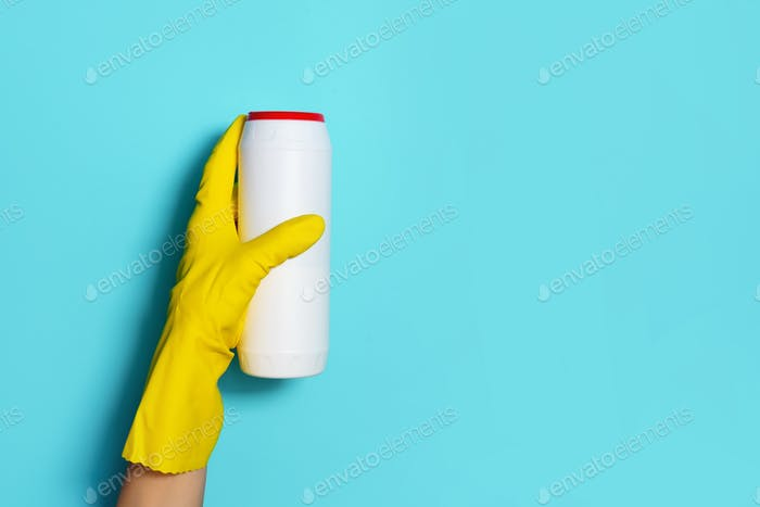 Hand in glove holding white plastic bottle of cleaning product, household chemicals. Copy space