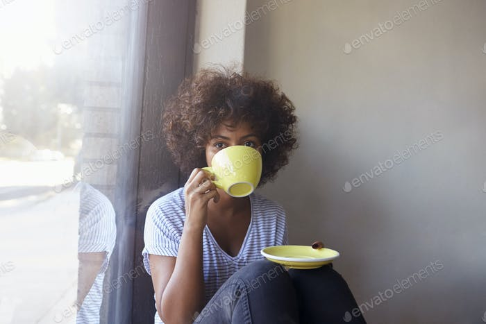 Young black woman sitting by window in cafe drinking coffee