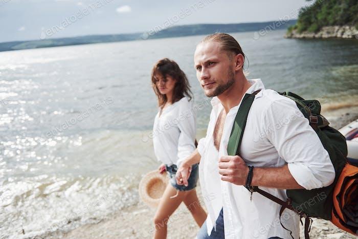 Niedlich jung und Paar auf Flusshintergrund. Ein Mann und ein Mädchen mit Rucksäcken reisen mit dem Boot