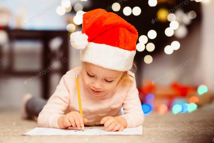 Niedliche Mädchen in Santa Hut schreiben Geschenke Liste für Eltern
