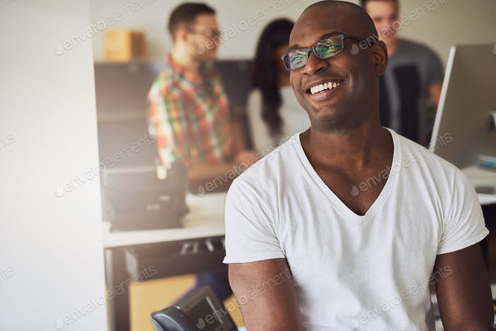 Thumbnail for Cheerful confident black businessman sitting in office