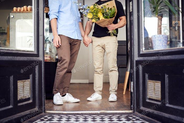 Nahaufnahme von liebevollen männlichen schwulen paar halten hände kommen aus floristen halten bündel von blumen