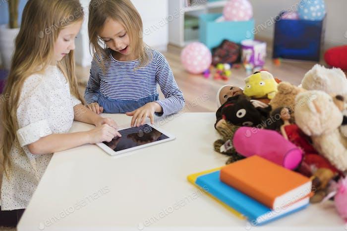 Little girls focused on interesting video game