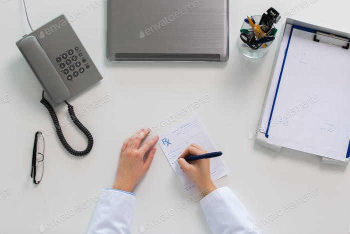doctor hands writing prescription at table