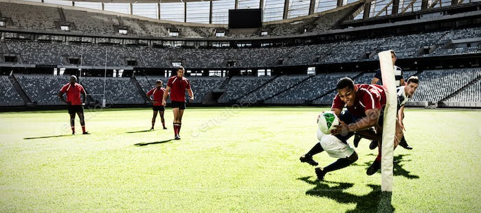 Digital composite image of two rugby players tackling each other in sports stadium