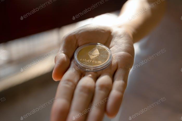 Joven sosteniendo la moneda ETH Ethereum en la palma de la mano