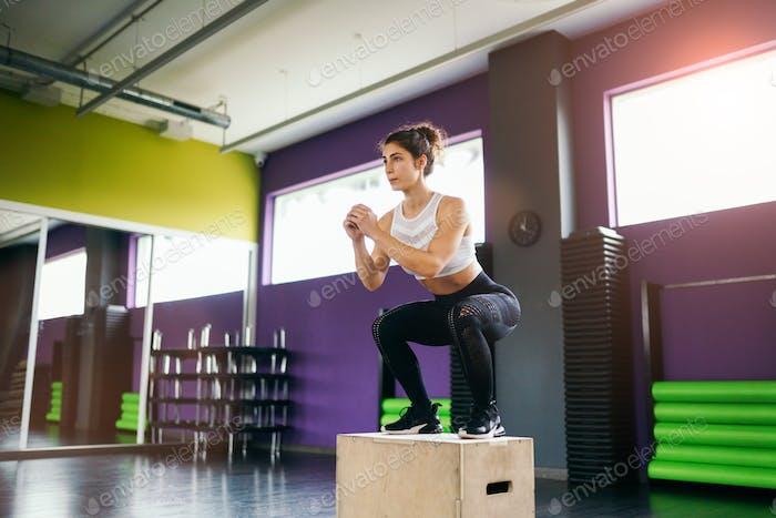 athletische Frau tun Kniebeugen auf Box in der Turnhalle