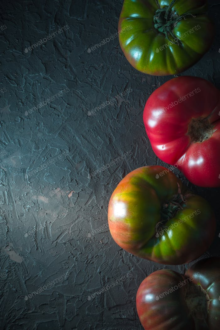 Multicolored tomatoes on a gray background line on the right