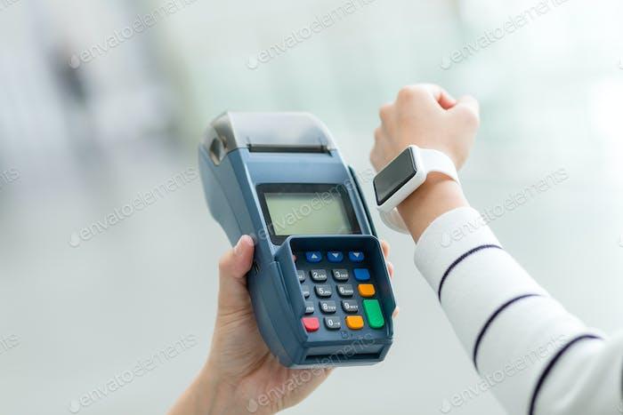 Frau mit Smart Watch, um mit NFC-Technologie zu bezahlen